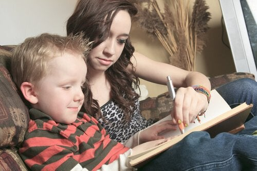 Teen helping a child with reading problems.