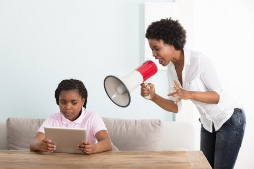 A mother yells at her child through a loudspeaker.