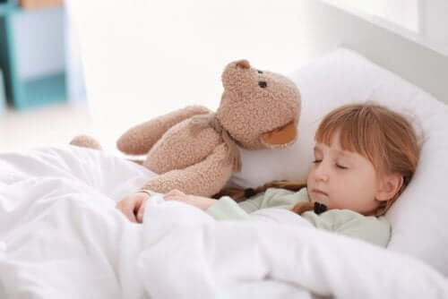 A girl napping with her teddy bear.