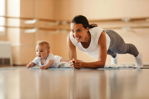 A baby imitating her mother exercising.