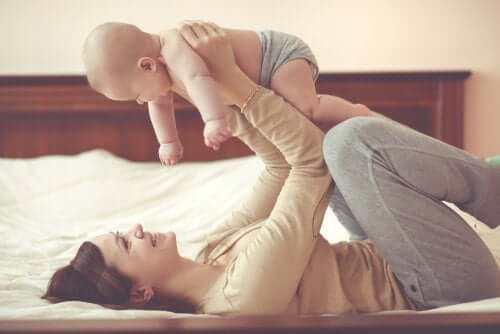 A mother playing with her baby on the bed.