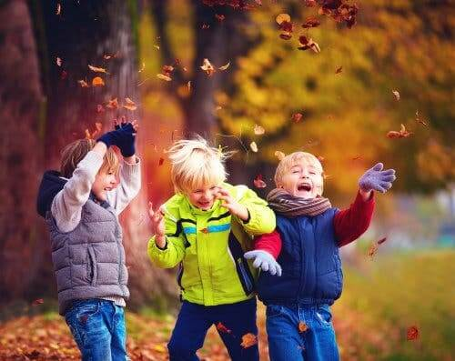 Three children throwing leaves.