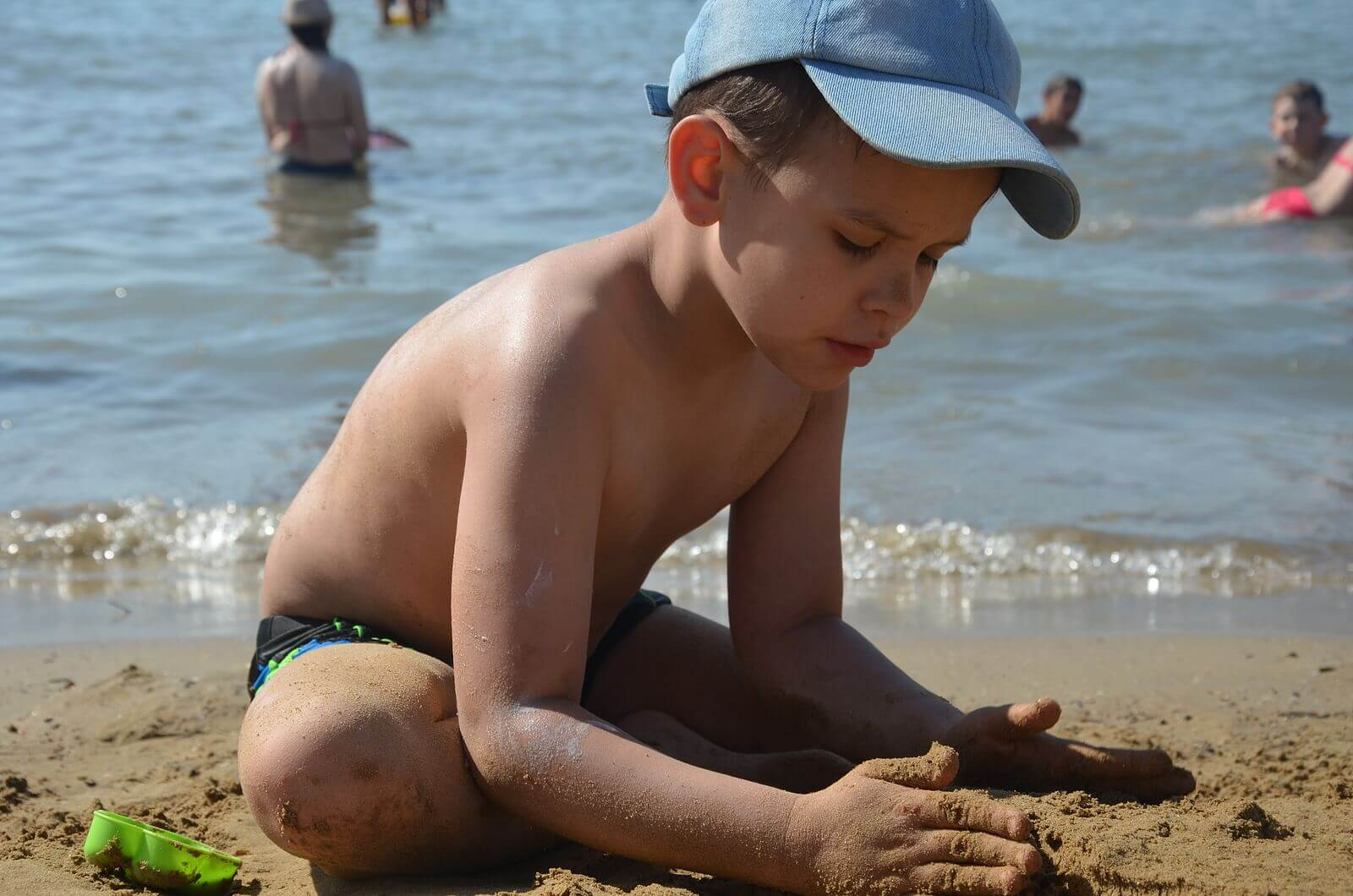 A child playing in the sand at the beach.