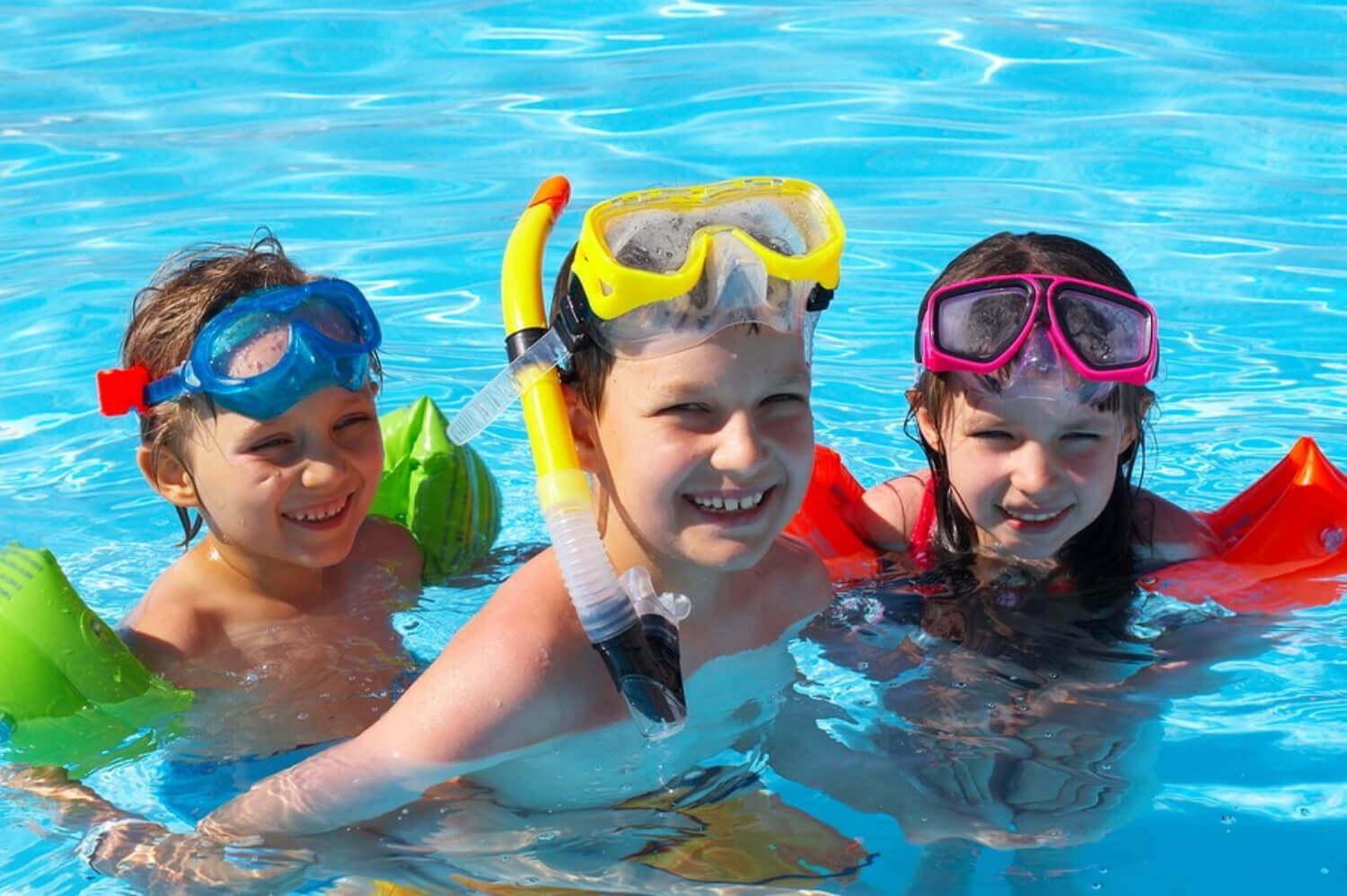 Children playing in a pool with snorkel gear.