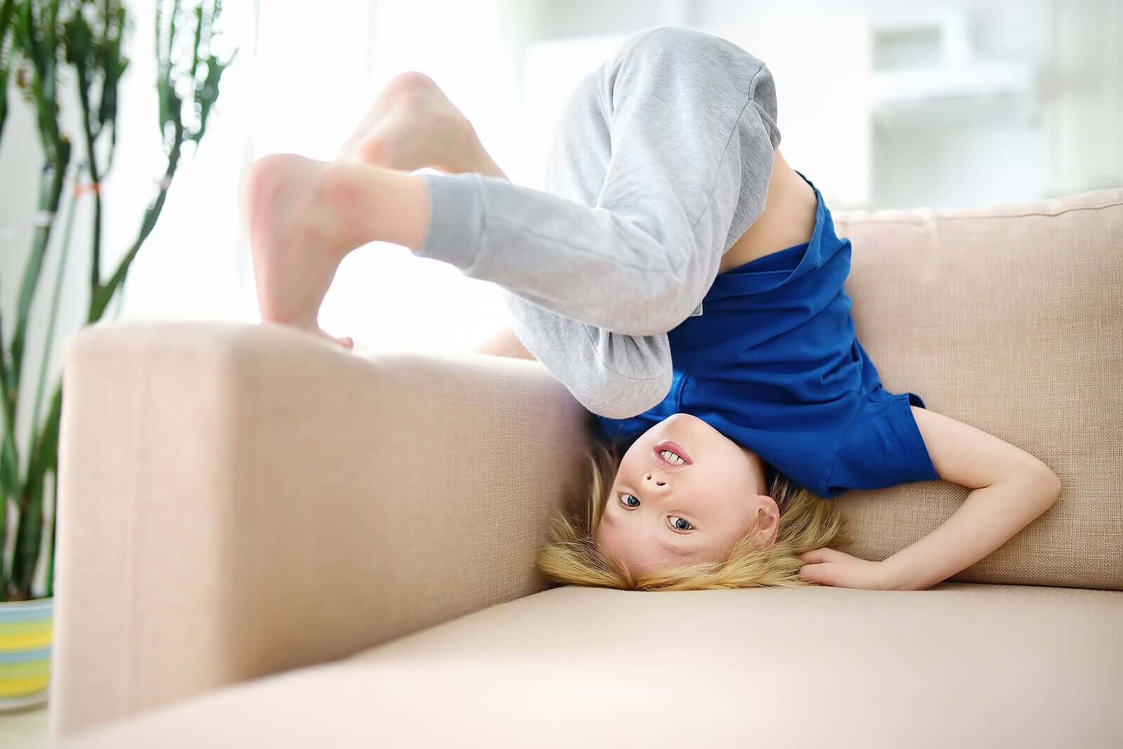 A child tumbling on a couch.