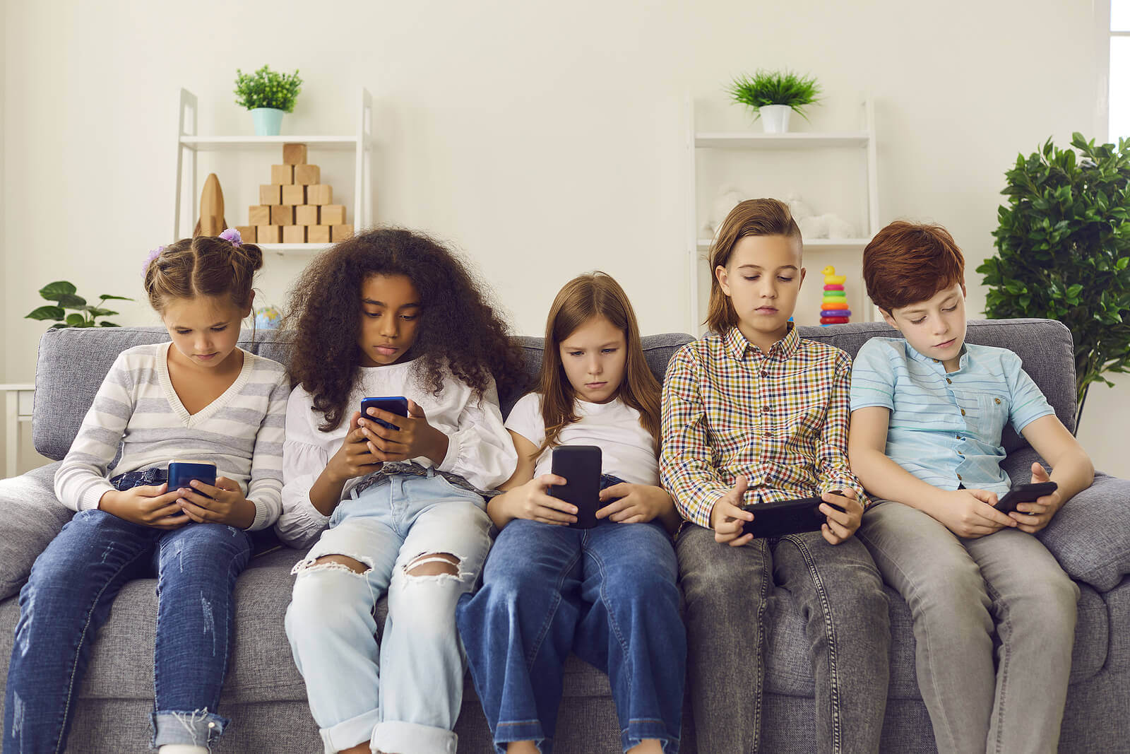 Five preteens sitting on the couch looking at their phones.