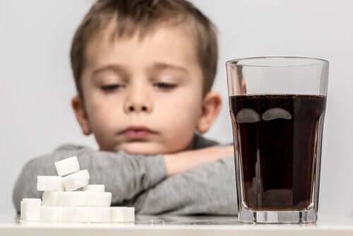 A small child staring at a pile of sugar cubes next to a glass of coke.