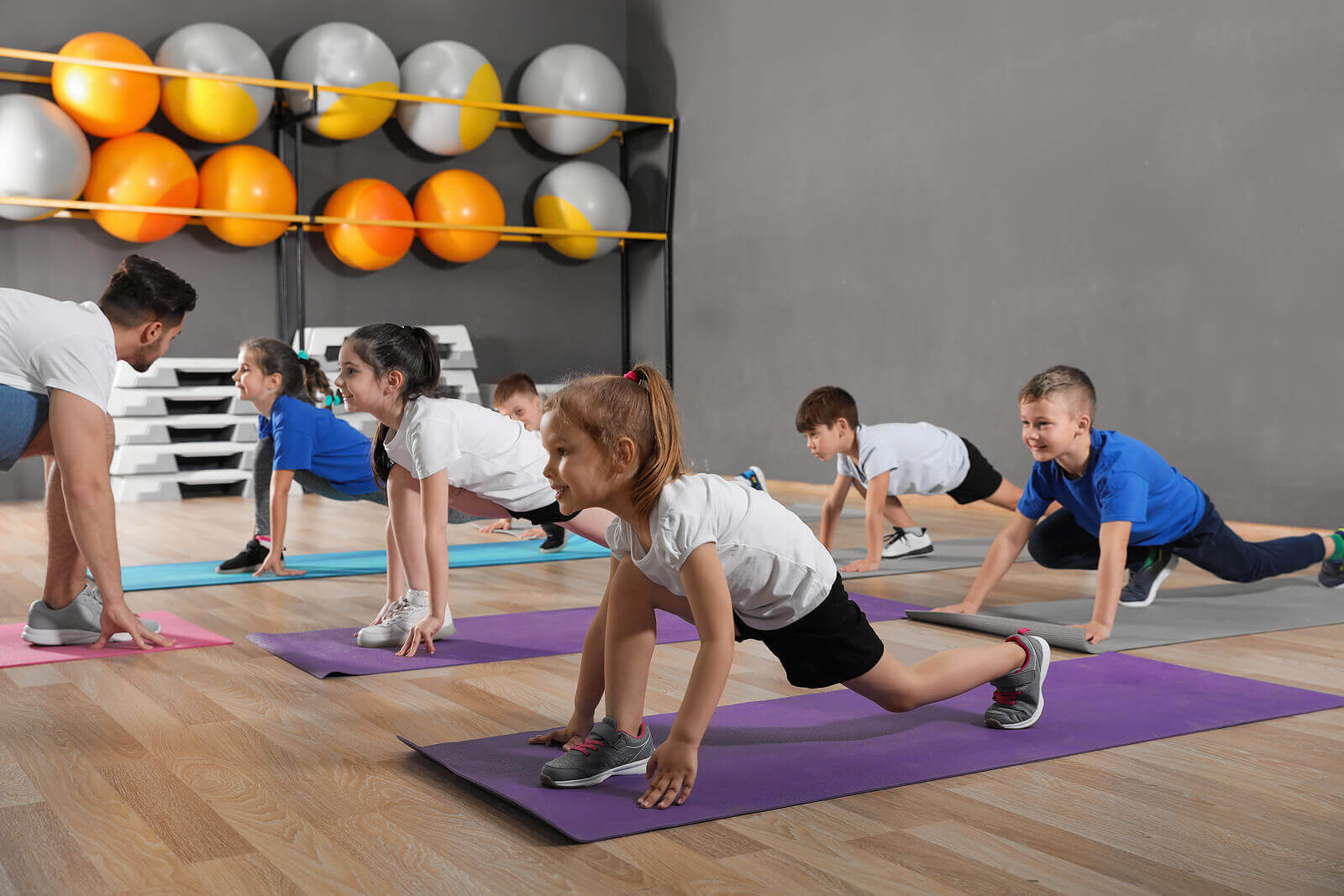 Children stretching on yoga mats in a gym.