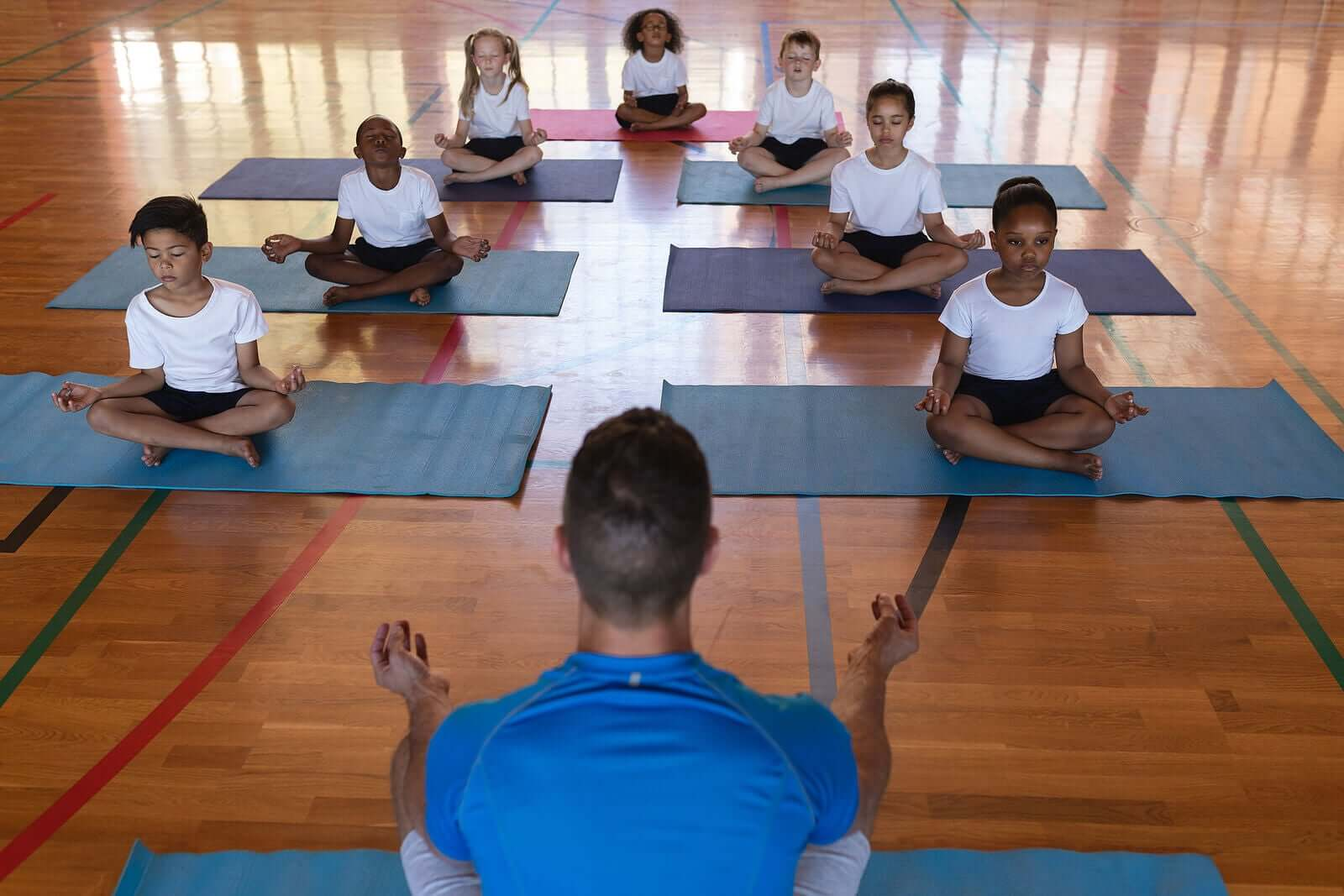 Children practicing yoga in a school gym.