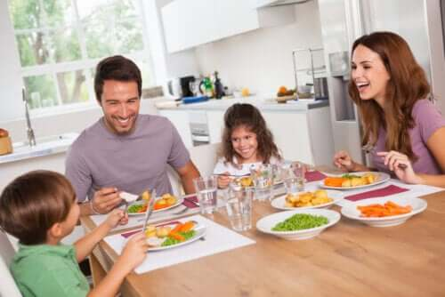 A family sitting down at the kitchen table eating a healthy meal and laughing together.