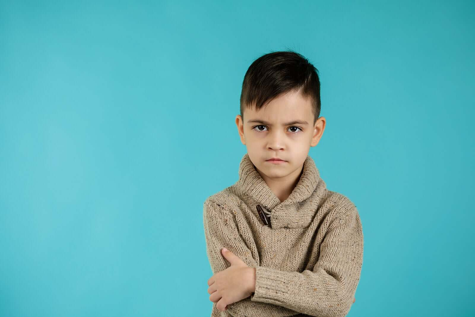 A small child crossing his arms and looking angry.