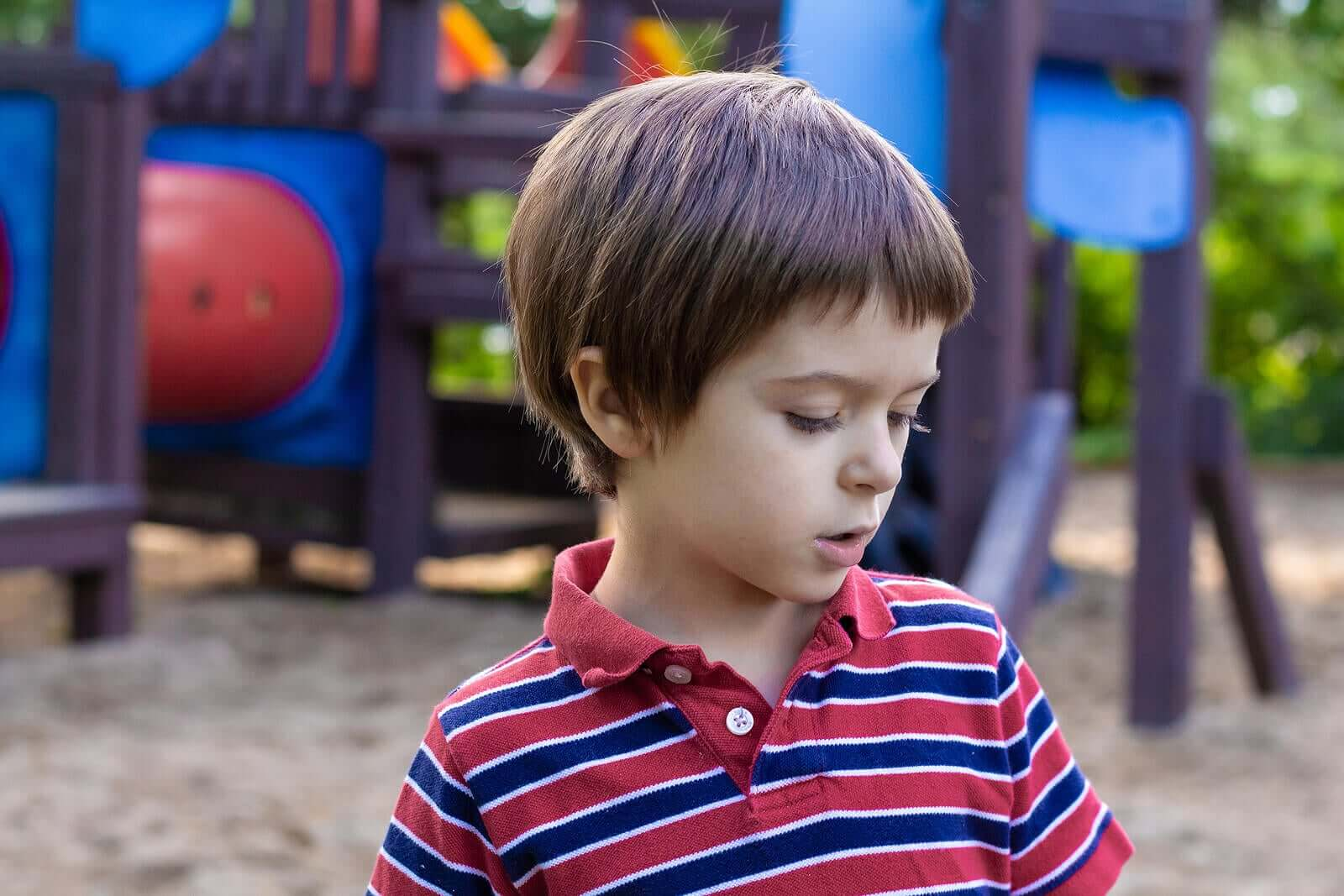 A child talking to himself on a playground.