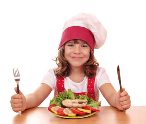 A smiling child sitting in front of a plate of fish and vegetables.