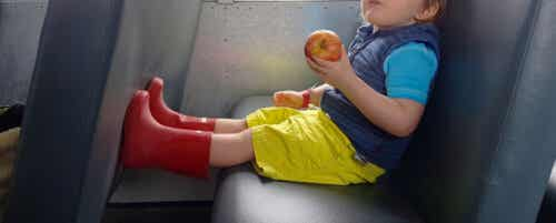 A toddler sitting on the bus eating an apple.