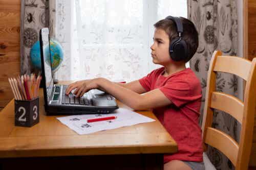 Dreng ved computer er ved at lære at skrive
