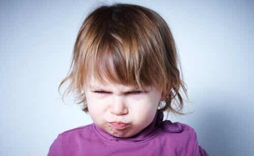 A two-year-old girl making an angry face.