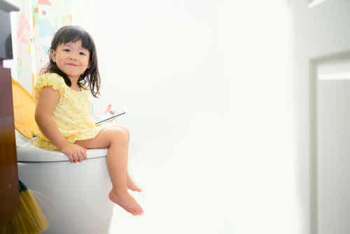 A toddler sitting on the toilet.