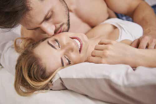 En man som kysser sin fru i sängen.