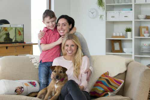 Two woman sitting on the couch with their son and their dog.