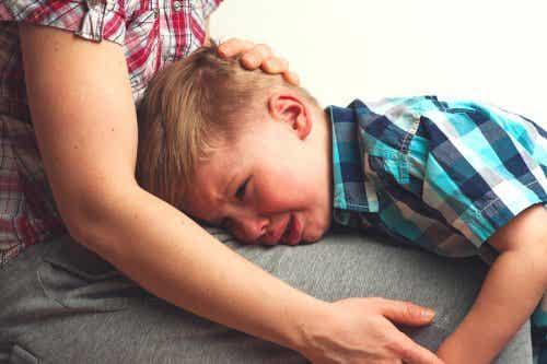 Een kleine jongen huilend op zijn moeders schoot.