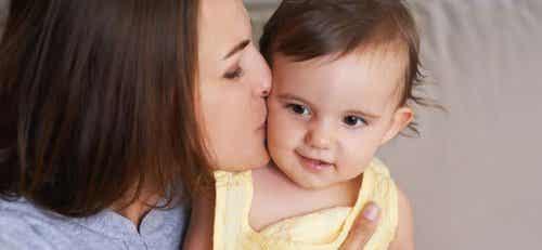 En mamma som pussar sitt barn på kinden.