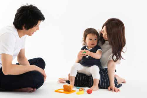 Ett par som leker på golvet med deras litet dotter.