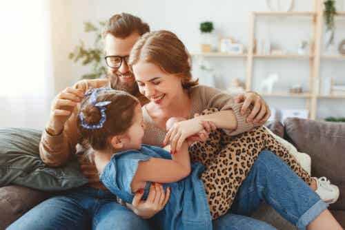 Föräldrar som leker med sin dotter i soffan.