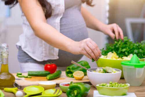 A pregnant woman preparing a salad.