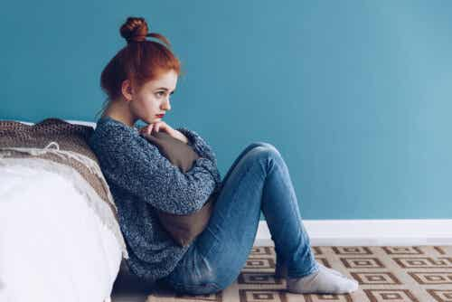 A teenage girl sitting on the floor next to her bed, hugging a pillow to her chest.