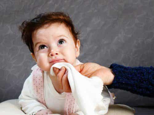 En hand som torkar spott från en babys mun.