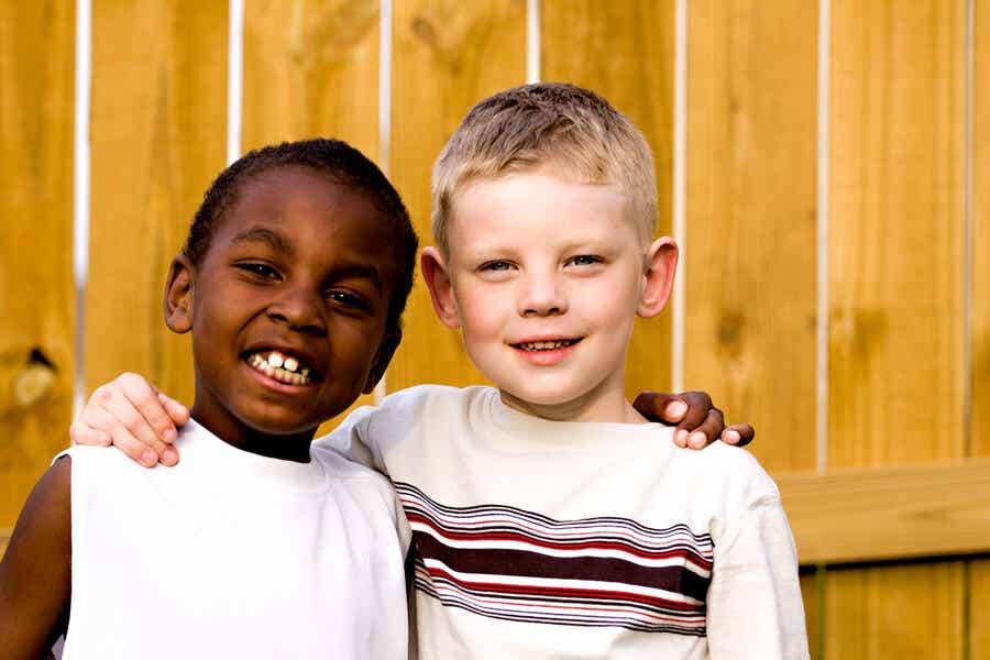 A black boy and a white boy with their arms around one another's shoulders.