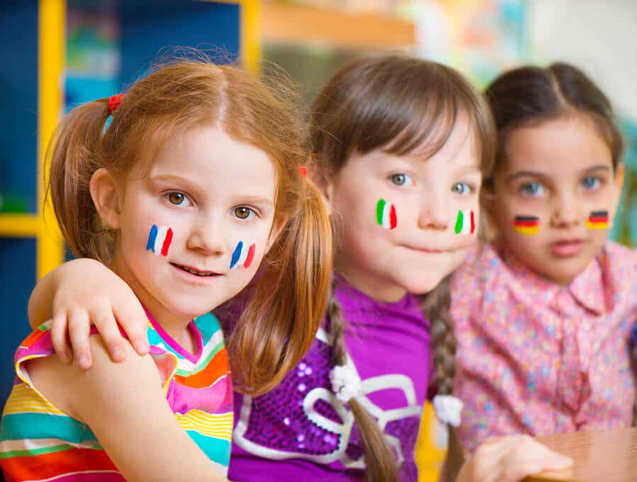 Three little girls with different flags painted on their cheeks.