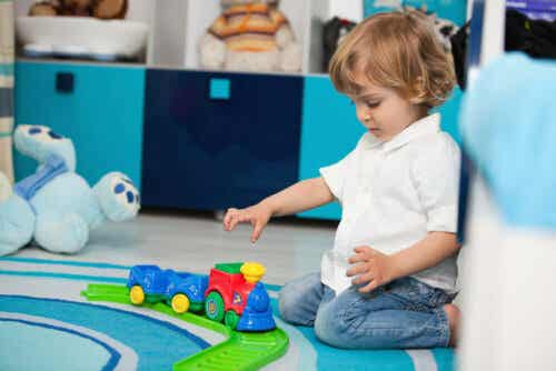 A 2-year-old playing with a toy train.