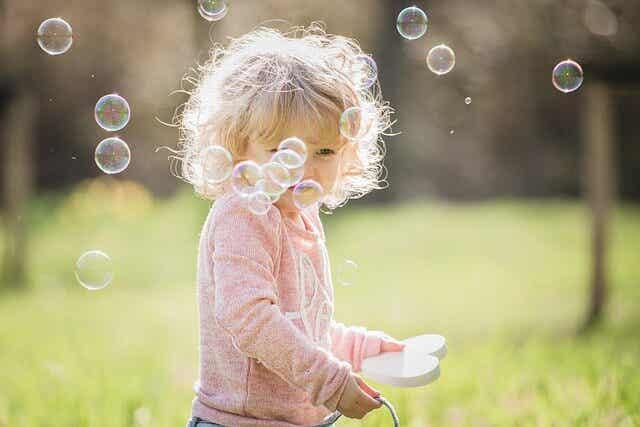 En flicka som blåser utanför bubblor.