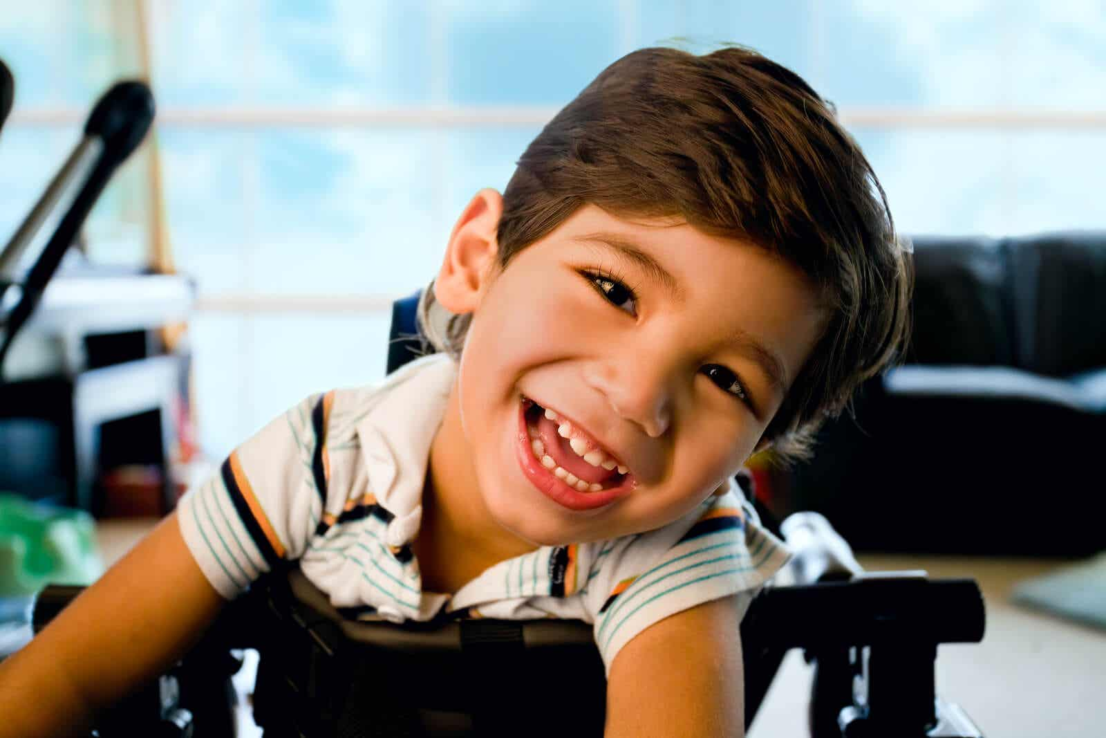 A smiling child leaning on his walker.