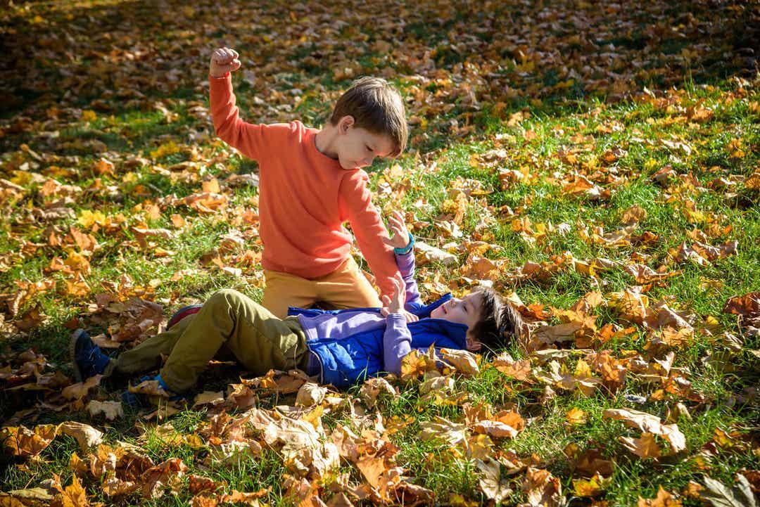 En liten gutt som holder en annen gutt på bakken og slår ham.