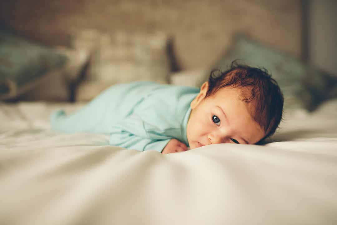 A newborn lying on his tummy on a bed.