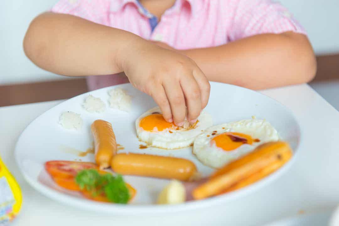 Een kind dat eieren en worstjes eet.