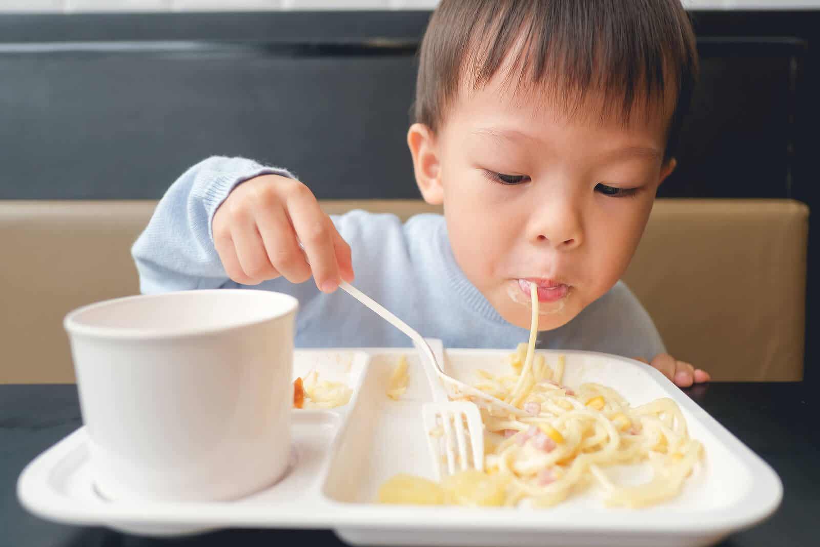 Ett litet barn som äter pasta.