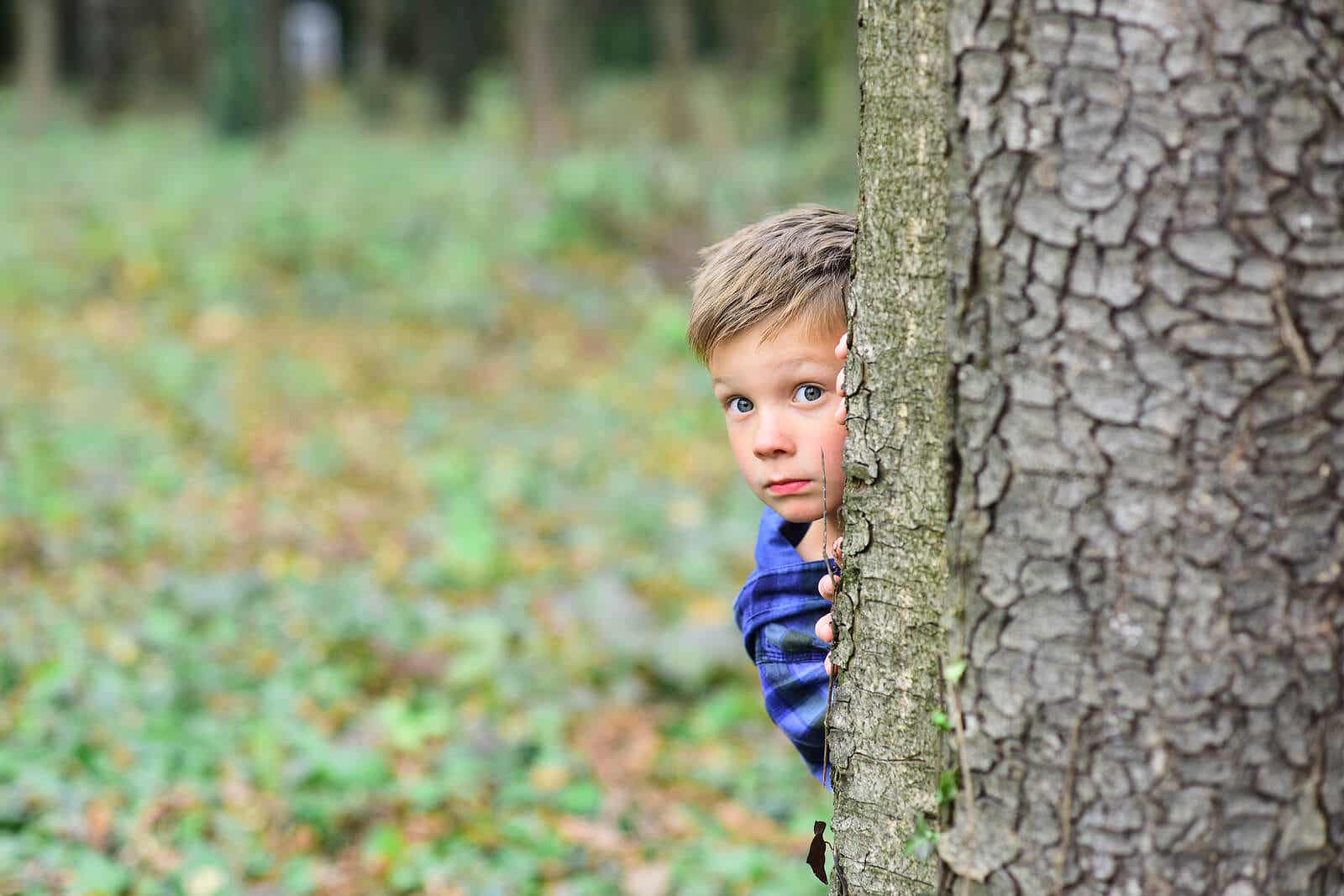 A child hiding behind a tree, looking scared.