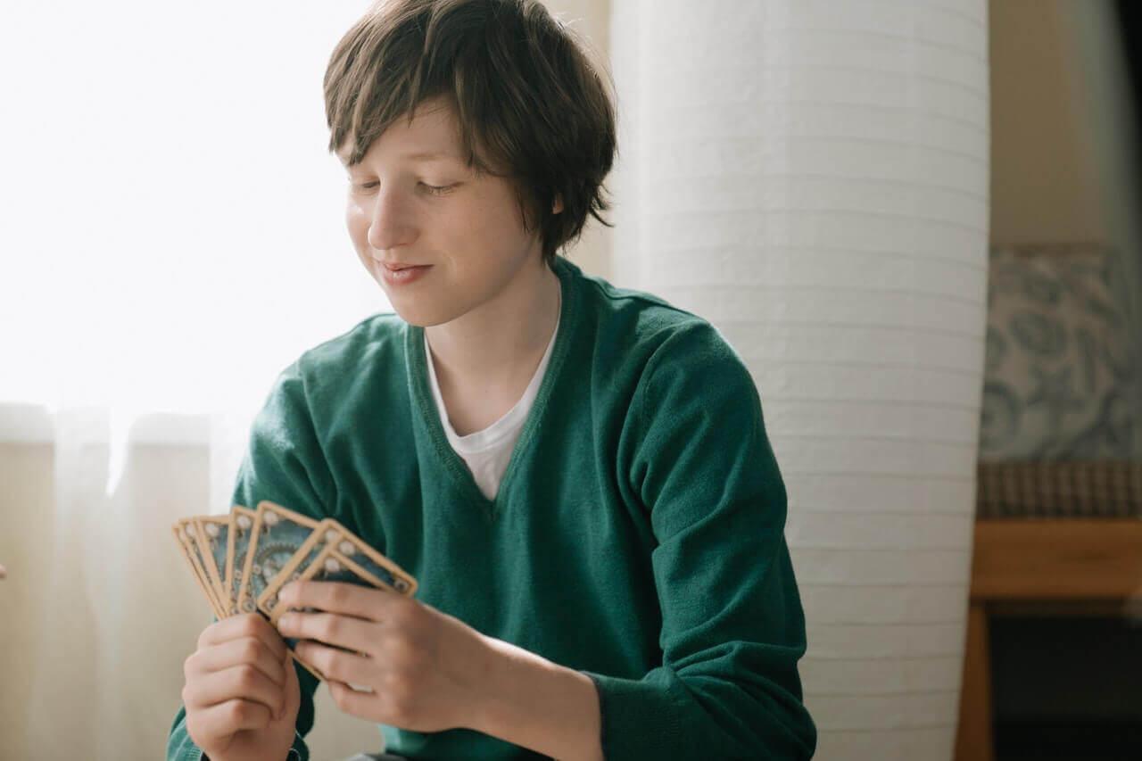 Nastolatek trzymający karty w ręce