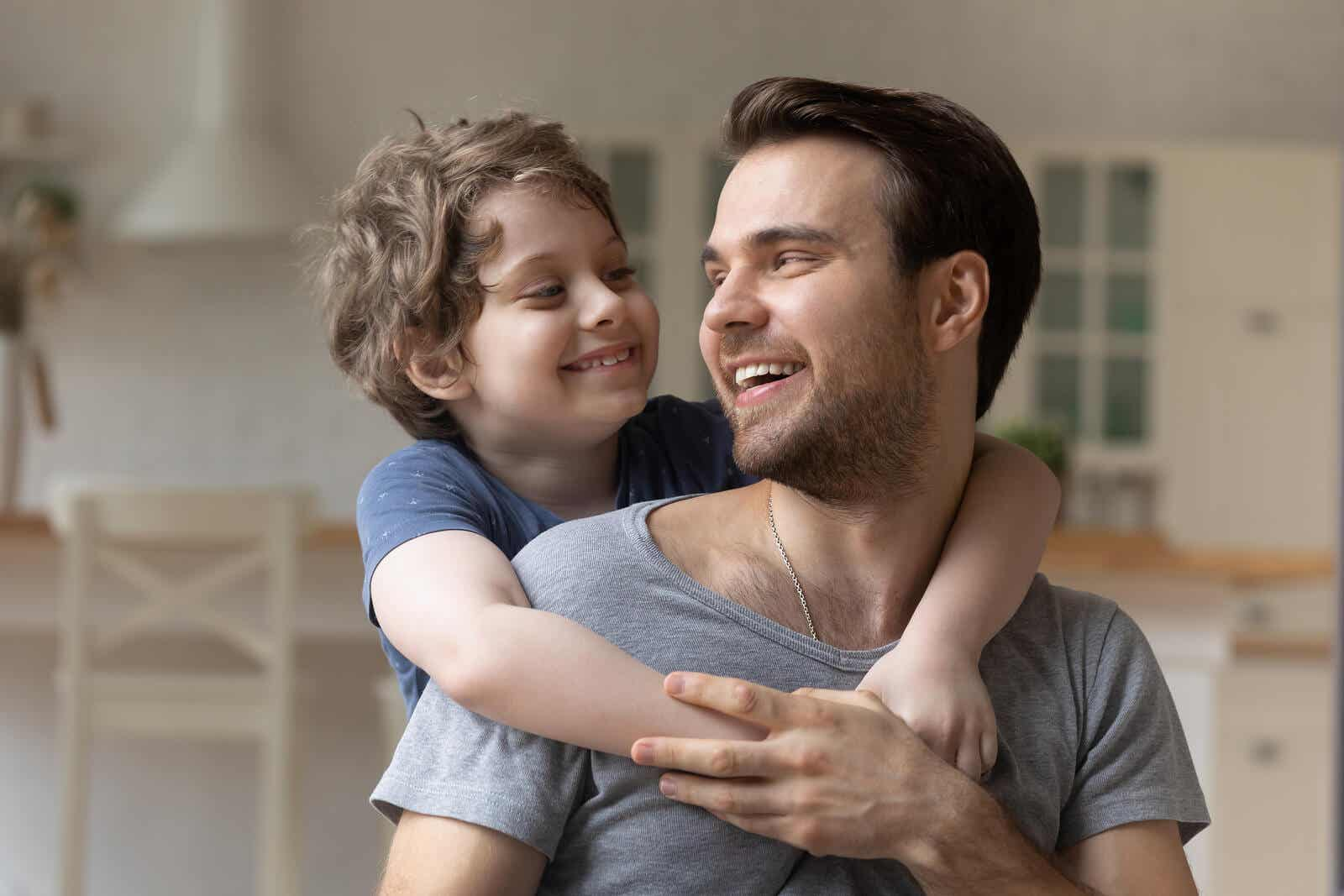 Een kind met zijn armen om de schouders van zijn vader terwijl ze naar elkaar glimlachen.