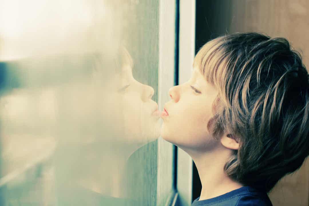 Een kind dat zijn kin op een raam laat rusten en naar buiten kijkt.