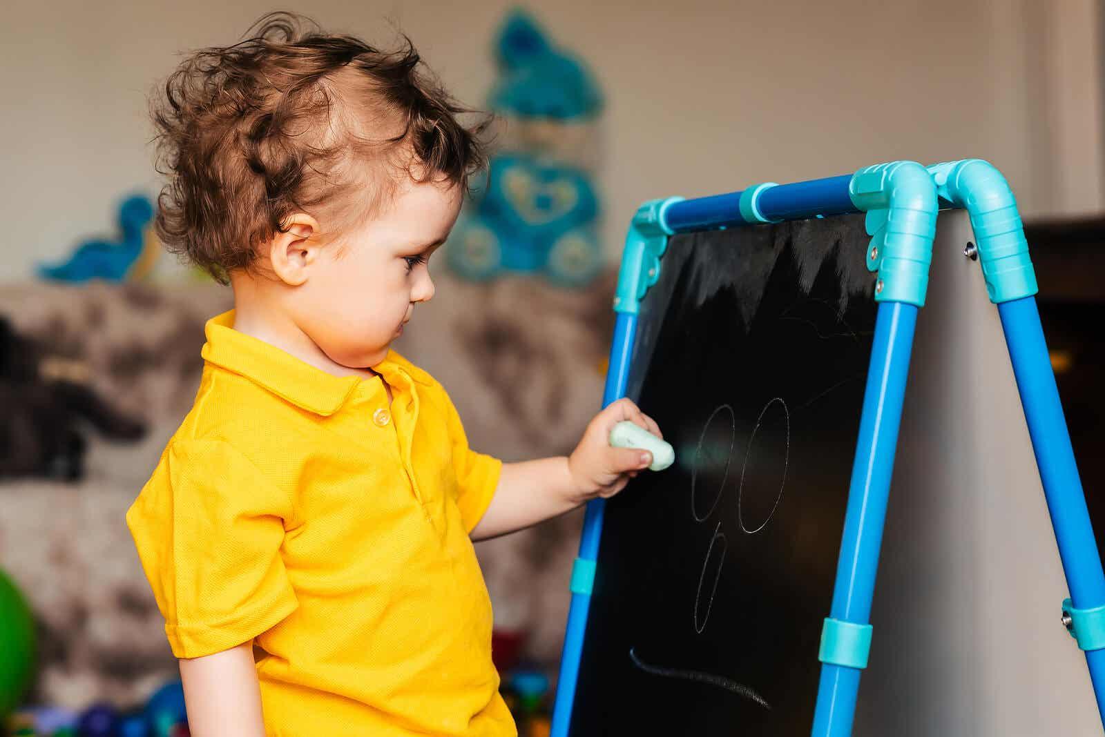 Ett litet barn ritar på en tavla.