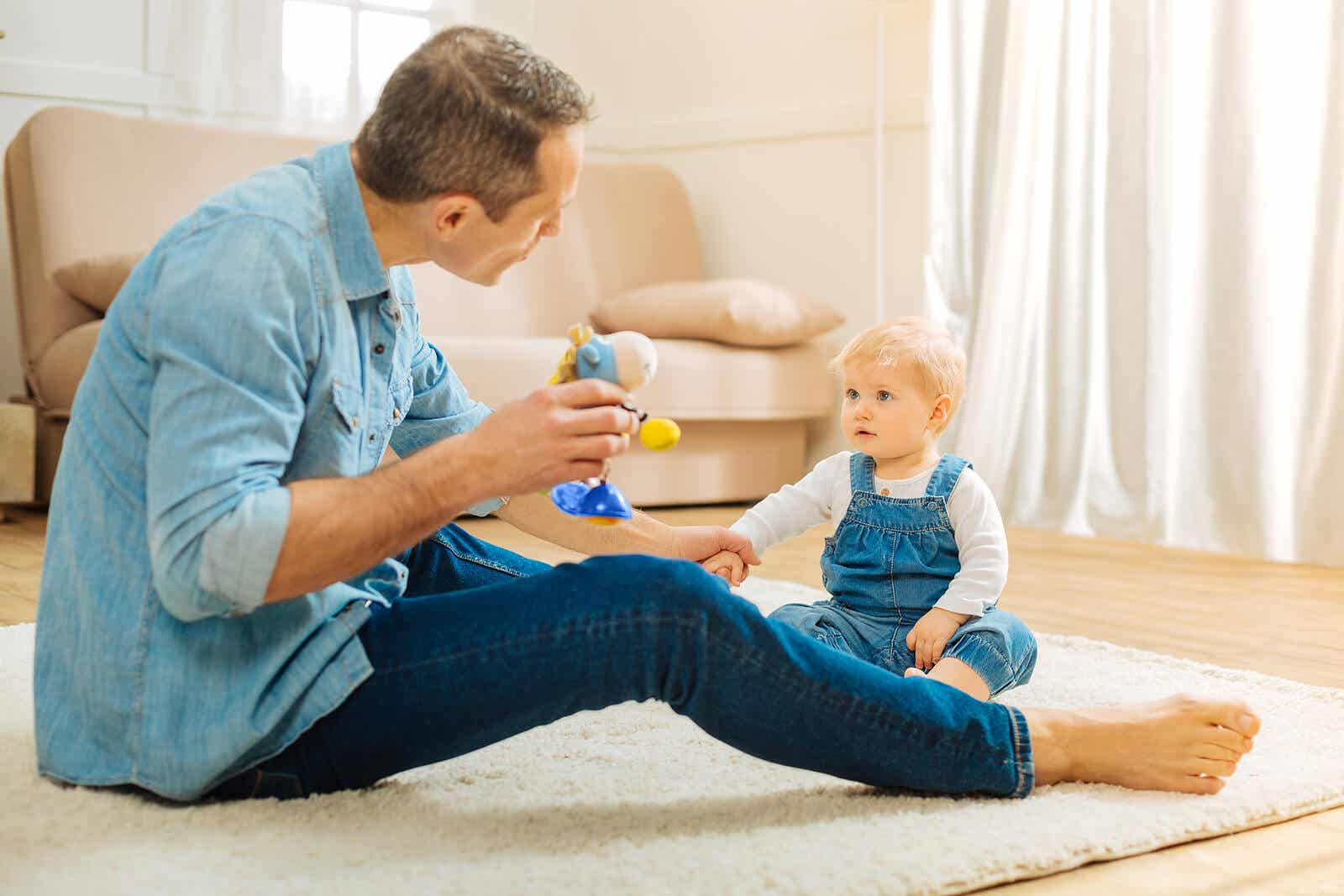 A father sitting on the floor and communicating with his baby girl.