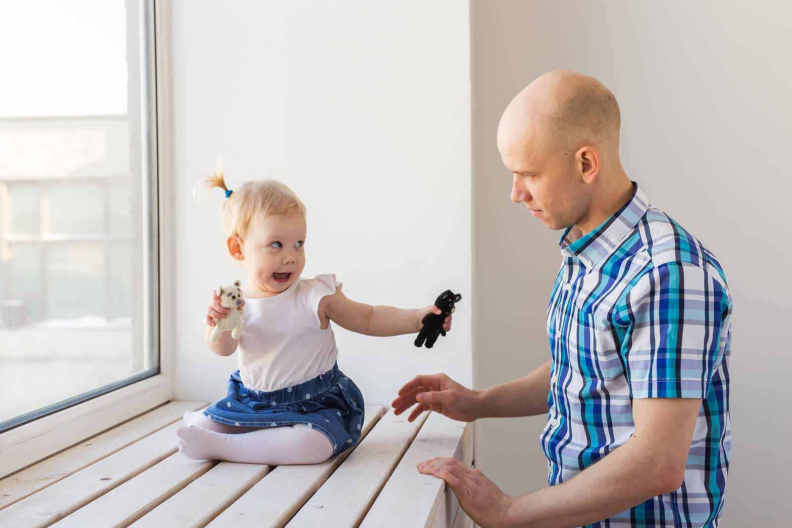 A toddler communicating with her dad.