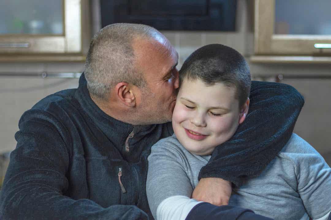 Een vader die zijn autistische zoon knuffelt en kust.