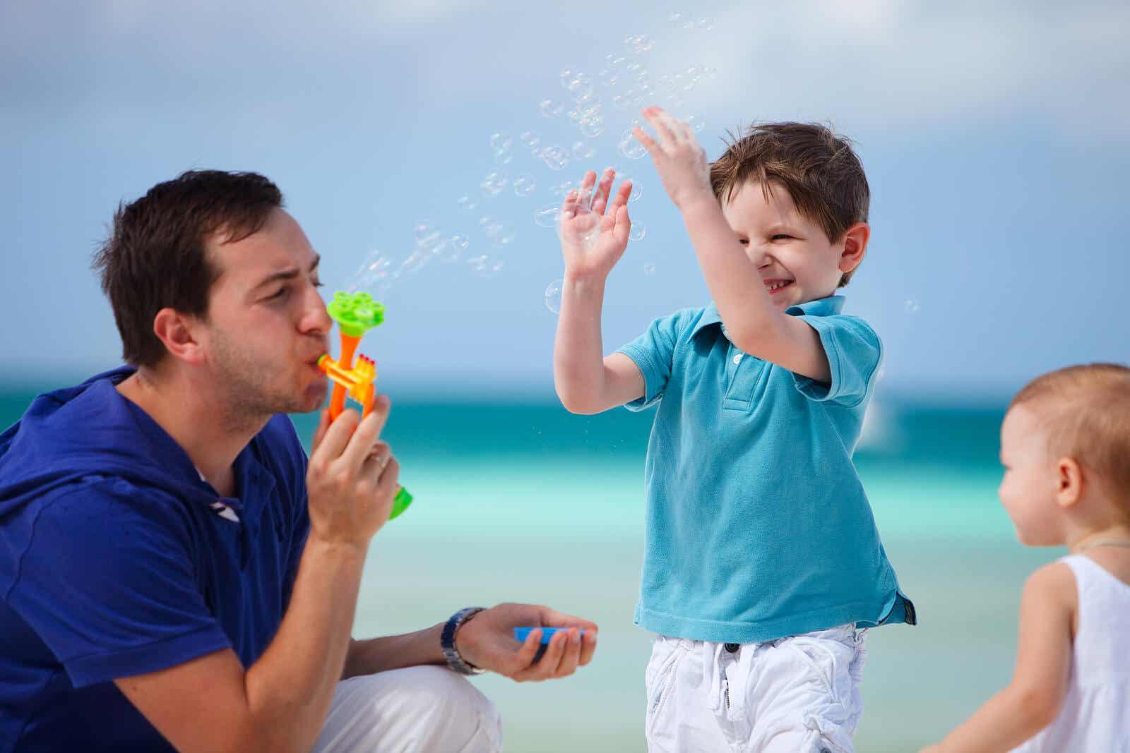 Een vader die met zijn kleine kinderen bellen blaast op het strand.