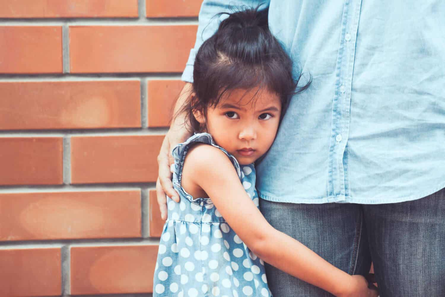 A small child hugging her parent's leg, looking afraid.