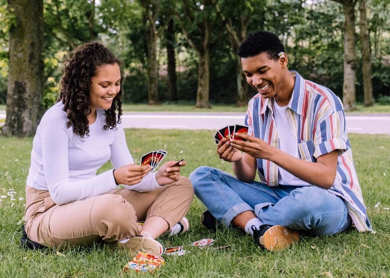 Para grająca w karty na trawie.